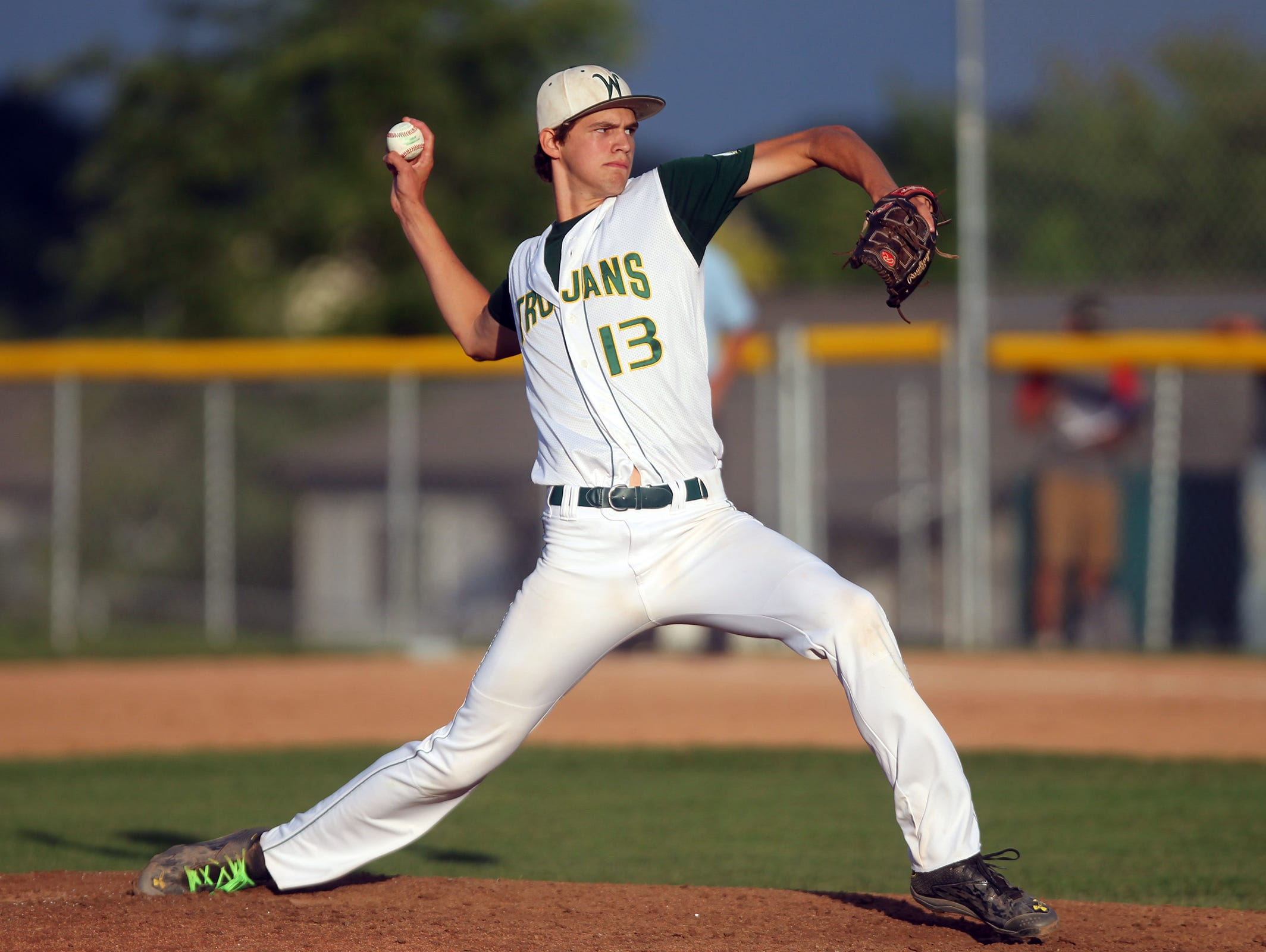 West High's Tanner Lohaus delivers a pitch during the Trojans' game against City High at West High on Tuesday, July 7, 2015.