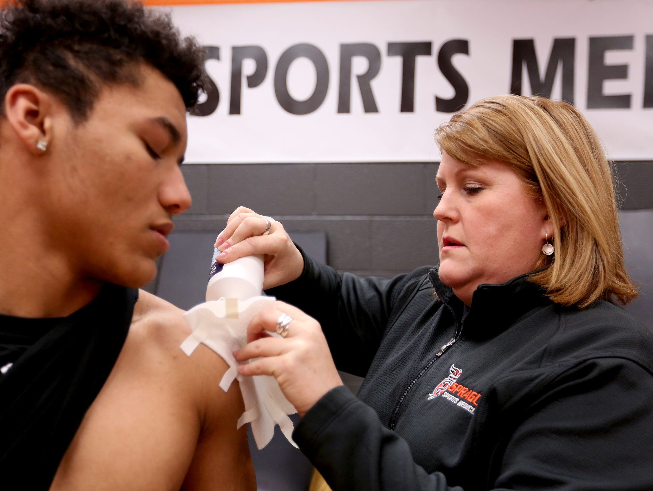 Athletic Trainer Amy West puts a bandage on the shoulder of Gejuan Lancaster, a freshman baseball player, at Sprague High School in Salem on Tuesday, April 5, 2016.