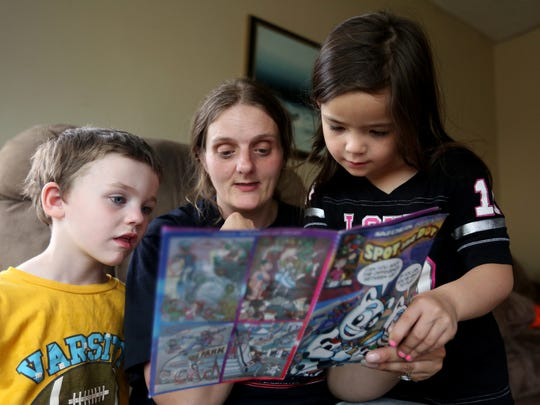 Melody Reitzer, 6, her mom and 5-year-old brother Nathan read a magazine at her stepfather's home in Salem on Wednesday, April 20, 2016. Melody, her mom and three siblings live at the Simonka Place women's and children's shelter in Keizer.