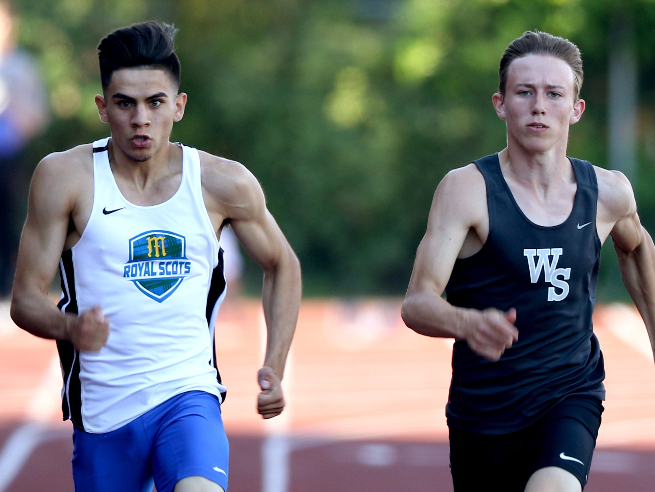 McKay's Israel Garza, left, and West Salem's Chase Lakin compete in the finals of the boys 100 meter dash at the Greater Valley Conference District Championships track and field meet at McMinnville High School on Friday, May 13, 2016. Garza placed first and Lakin second.