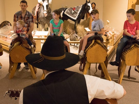 Children listen to a museum employee dressed as a cowboy play guitar Saturday, Feb. 11, 2017, at the Corpus Christi Museum of Science and History during a celebration of the 150th anniversary of the Chisholm Trail.