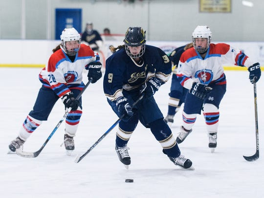 Essex's Olivia Miller-Johnson (9) skates down the ice with the puck past CVU-MMU's Nicole Wright (7) and Kiley McClure (20) during the girls hockey game between the Essex Hornets and the CVU-MMU Cougarhawks at the Essex Skating Facility on Wednesday night December 13, 2017 in Essex.
