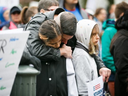 Travis Fanucchi embraces his nieces Chloe, left, and Gracie Rogers, right, at the March for Our Lives rally on Saturday, March 24, 2018, at the Oregon State Capitol. Over 2,000 people joined the student-led event, which called for stricter gun laws in the wake of the Parkland, Fla., shooting.