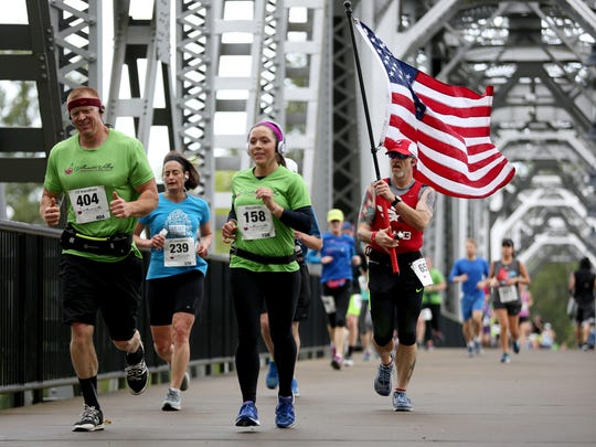Dean Chambers, 52, of Salem, carries an American flag during the Willamette Valley Marathon and Half Marathon in Salem on Sunday, May 6, 2018.