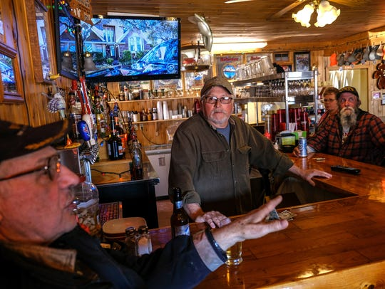 "Ben Galarowic (left), of Goetzville, talks about the area while sitting at Raber Bay Bar in Goetzville with owner Rich Harmon (center) on Saturday, April 28, 2018 in Michigan's Upper Peninsula.""This is a Yooper Bar,"" Harmon said. ""It's been here forever. It's quaint, it's out of the way. It's a fishing area, so we sell a lot of fish."""