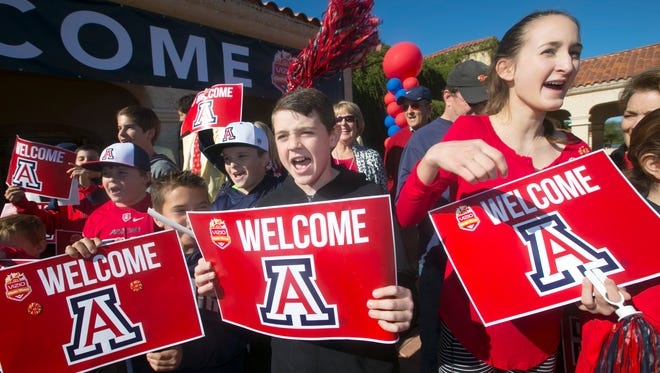 UA fans Drew Boxwell, 11, (center) of Scottsdale, Natalie Rink, 13, (right) of Scottsdale and others cheer as some members of the UA football team arrive at the Scottsdale Plaza Resort on Friday, December 26, 2014. UA plays Boise State in the Fiesta Bowl on December 31, 2014 at University of Phoenix Stadium in Glendale.