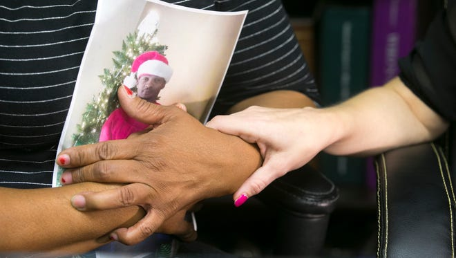 Nora Brisbon, (left) the mother of Rumain Brisbon, clutches a photograph of Rumain Brisbon, as  Brisbon's girlfriend, Dana Klinger, holds Nora's hand, while speaking to the media at their attorney's office in Phoenix on Thursday, Dec. 4, 2014. Brisbon was shot and killed by a Phoenix police officer.