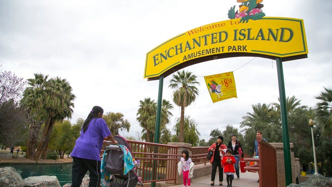Children and adults enter underneath the main gate at Enchanted Island Amusement Park in Phoenix.