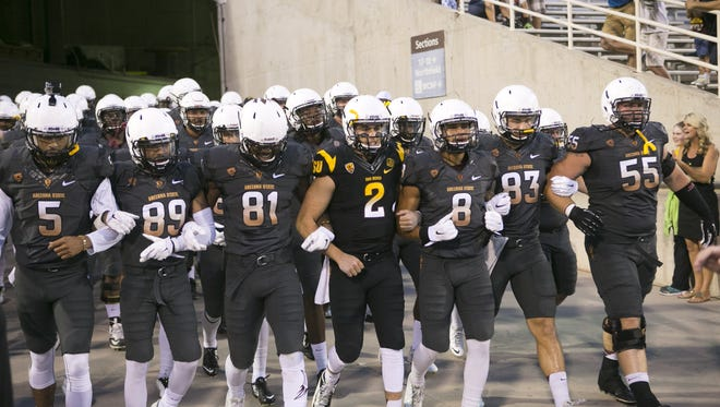 The ASU football team takes the field for the annual ASU Spring football game at Sun Devil Stadium in Tempe on April 10, 2015.