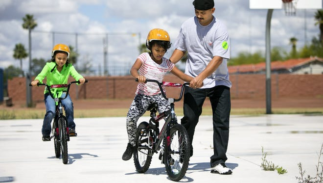 Volunteer, Jose Garcia helps steady Ruth Woldemariam, 8, of Phoenix as she rides her bike at the Build-A-Bike event.