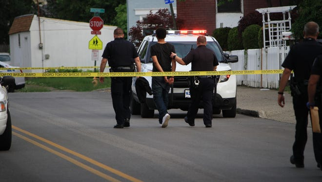 Covington police lead away a male in handcuffs. At least one arrest was made during the department's investigation of a Friday shooting at the intersection of Pike Street and Holman Avenue.