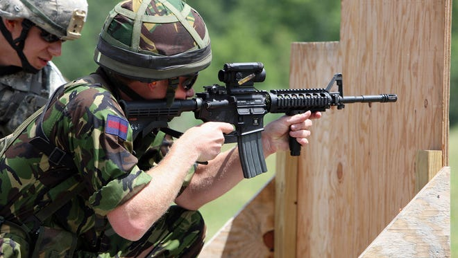 Britain's Prince Harry fires a Colt M4 assault riffle on a United States Military Academy range in West Point, N.Y.,  in 2010