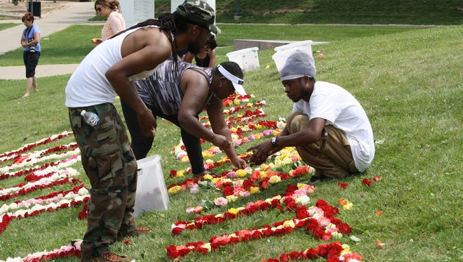 Volunteers place roses on UC campus in a memorial of Samuel DuBose.