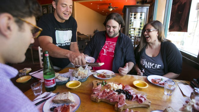 """The new Arizona Republic/ azcentral.com food critic Dominic Armato (second from right ) eats from a plate of meats, cheeses and olives as he hangs out with members of """"Phx food nerds"""" (from left) Chris Galli, Nick Hoyt and Cristen Burrell (far right) at Andreoli-Italian Grocer in Scottsdale on Thursday, August 6, 2015."""