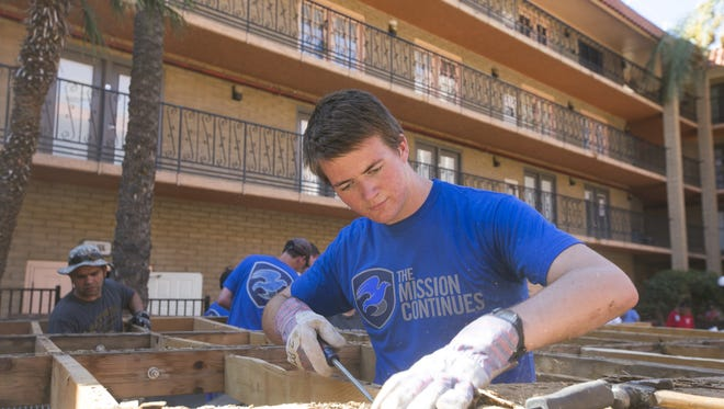 """Josh Kennedy, 17, of Chandler and the Lindsay 2nd Ward of the LDS Church, removes an old and dilapidated stage  at the Phoenix Dream Center, a Phoenix transitional housing complex, on Saturday, August 29, 2015. Volunteers with """"Mission Continues"""" a veteran volunteer group and church groups did work at the housing complex."""
