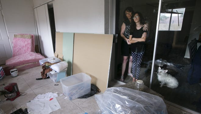 Karen Gleason and her daughter, Sofia Ochoa, 11, are seen looking out into the Arizona Room that has still not be completely fixed at their home in Mesa on Aug. 27, 2015. The Gleason's home was severely damaged by flood waters that inundated the Mesa neighborhood on Sept. 8, 2014. Karen and Sofia were unable to live in the home for six months.