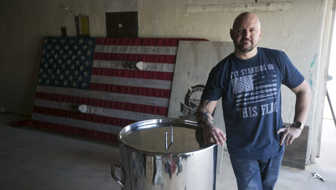 Christopher Lucidi, founder and distiller of the Lucidi Distilling Company at the historic Fire Station No. 1, is seen next to a distilling tank in front of the fire station in old town Peoria on Saturday, September 5, 2015. Lucidi is turning the old fire station into a distillery and a tasting room with adjacent restaurants that he also plans to build.