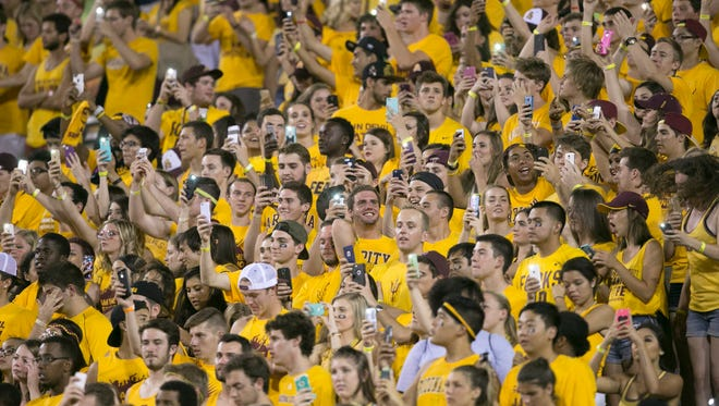 ASU fans hold up the lights on their smart phones during the third quarter of the college football game between ASU and Cal Poly at Sun Devil Stadium in Tempe on Saturday, Sept. 12, 2015.