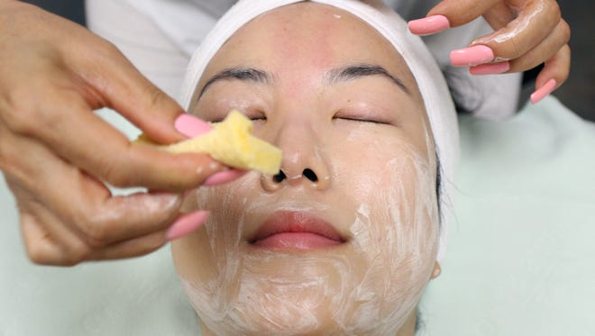 Skye Shin of Entre Nous Salon performs a facial on Yunee Kim using Korean skin care products on Sept. 8.