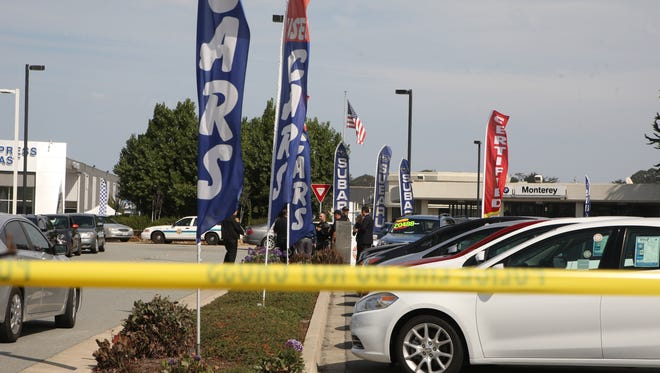 Investigators work the scene of an officer-involved shooting at the Auto Center in Seaside Wednesday.