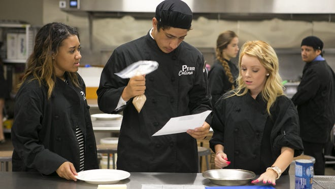 Zarria Sanders, 17, (from left) Noah Lata, 16, and Caylee Huntley, 17, make monkey bread in culinary class at Perry High School in Gilbert on Friday, Oct. 16, 2015.