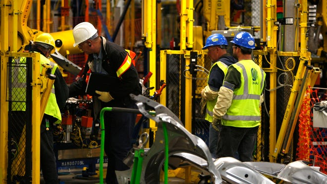 Contractors look over a robotic assembly at the Orion Assembly in Orion Township, Mich.,