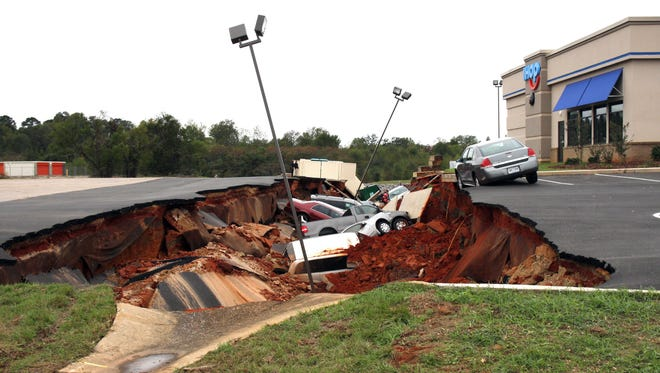 This photo shows vehicles after a cave-in of a restaurant parking lot in Meridian, Miss., Sunday, Nov. 8, 2015. Experts are to begin work Monday seeking to determine the cause of the Saturday collapse, authorities said.