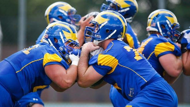 Justin Glenn (left) tangles with fellow offensive linemen in University of Delaware preseason drills in 2014.