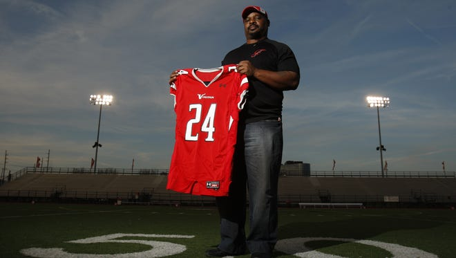 In this 2010 file photo, former Bengals star Ickey Woods holds the football jersey worn by his son Jovante, who died at 16 from an asthma attack. Ickey Woods donated $100,000 Monday to Cincinnati Children's Hospital Medical Center for asthma research