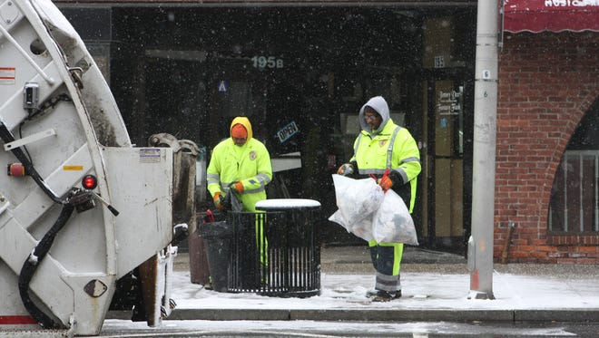 White Plains sanitation workers collect garbage while snow falls on East Post Road on Friday, March 4, 2016.