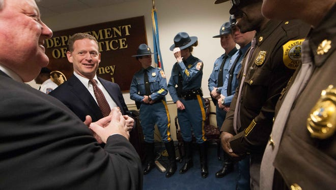 Delaware Attorney General Matt Denn talks with state troopers and New Castle County officers at an event on Jan. 12, 2015, in Wilmington. Denn and lawmakers are rallying behind a proposal that would eliminate the rule that schools have to report minor fights between students to the police.