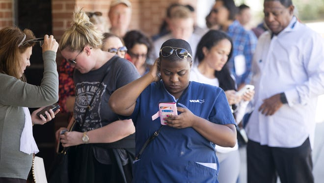Audrey Weaver, center, of Phoenix waits in line with others to vote in the Arizona primary at the polling place at Memorial Presbyterian Church at 40th Street and Thomas Road in Phoenix on Tuesday.