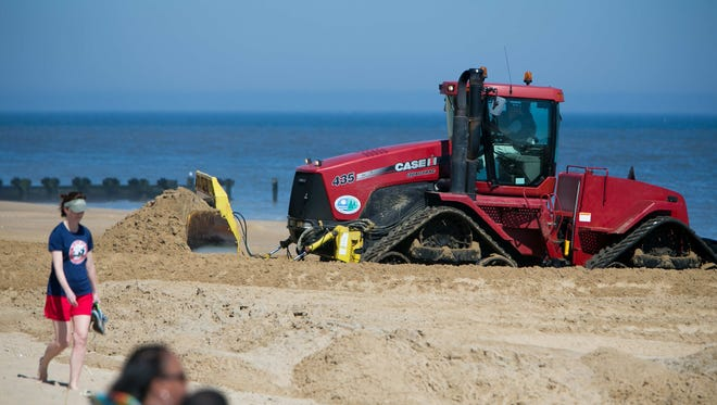 A bulldozer pushes sand at Rehoboth Beach during an unseasonably warm day on March 9. Conservation group Oceana is calling for a halt to seismic testing in the area off the Delaware coast to Florida