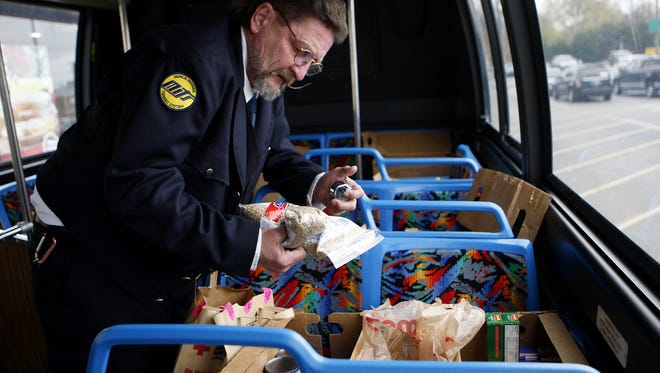 A MITS employee counts and loads donated groceries onto a MITS bus as part of a past Stuff-A-Bus collection for Christian Ministries.