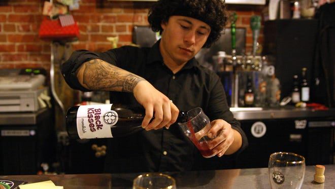 """The bartender pours tastings of Monkfish Brewing Co.'s """"Black Kisses"""" during """"Pint Night."""""""