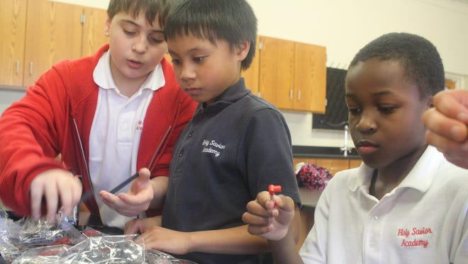 Holy Savior Academy students -- from left, Michael Robitaille, third grade, 9; Rainart Chioco, 5th grade; and Liam Franklin, fourth grade -- work on building a robot during the school's newly created Robotics Club.