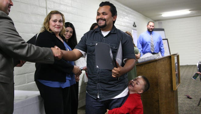 Javier Ramirez's young son giggled while clutching his father's leg as Ramirez walked up to receive a certificate signifying that he successfully completed the Monterey County Day Reporting Center's re-entry program.