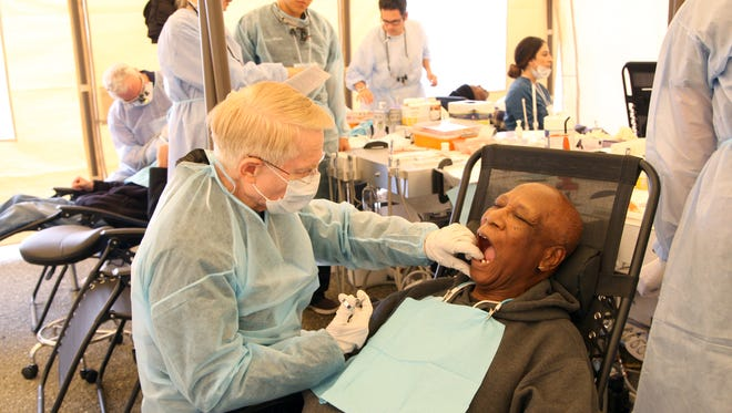 Salinas dentist Dr. Mark Washburn volunteers services for veterans like Jesse Knight of Marina during the Monterey County Homeless Stand Down for Homeless Veterans on Saturday.