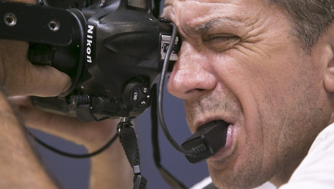 Loren Worthington, who is quadriplegic, bites on a cable release attached to his camera to trigger the shutter and take sports photographs.