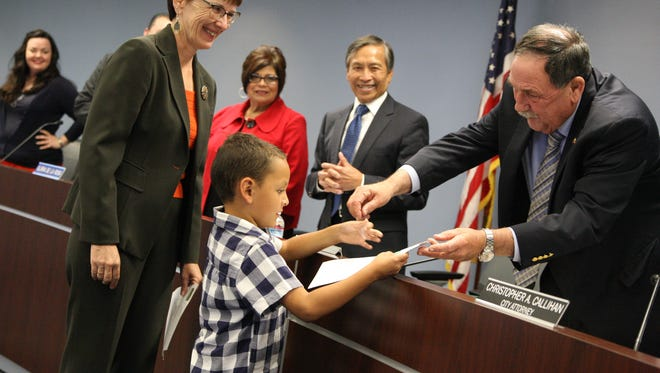 Kindergartner Miguel Angel Ortiz received his first library card from Salinas Mayor Joe Gunter on Tuesday night.