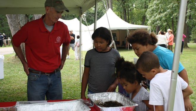 Kevin Mathers (left), Resource Educator, of Cornell Cooperative Extension, shows kids the kind of creatures that live in composts.