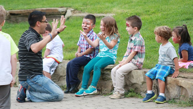 Israel Flores entertains a group of kids with magic tricks during Hispanicheritage Festival at Friendship Park Saturday afternoon