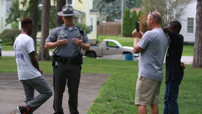 """Ohio State Highway Patrol Trooper Jordan Schwochow, of Fremont, explains to Jaden Robinson the possibility of becoming a trooper while Mayor Danny Sanchez records the conversation. The Fremont Police Department and the Sandusky County Sheriff's Office sponsored a """"Fun Day with Cops"""" event Sunday at Birchard Park."""