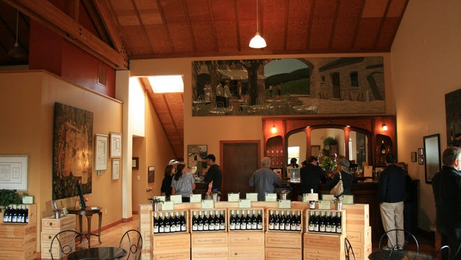 Vistors enjoy sampling wine in the warm, open and inviting atmosphere of the tasting room at WillaKenzie.