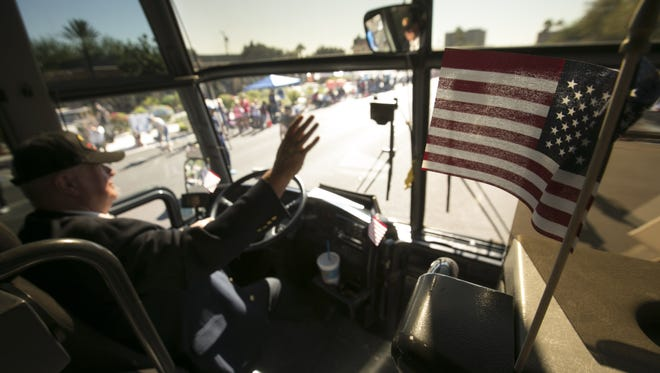 Vietnam War veteran and Tour West America charter bus driver Terry Sparbel waves to the crowd while driving in the Phoenix Veterans Day Parade on Nov. 11, 2016. Tour West and the Phoenix VA Medical Center teamed up to allow a handful of veterans to ride.