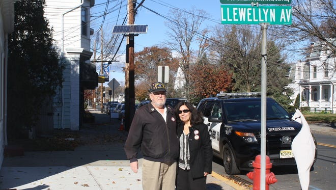 Private William P. Anderson's family members Sandy Anderson and Joan Goll pose under the street dedication on the corner of Llewellyn and Lafayette Avenue on Veteran's Day in Hawthorne.