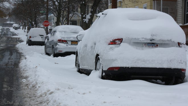 Cars on Ayres street in Binghamton were blanketed in snow Monday morning.