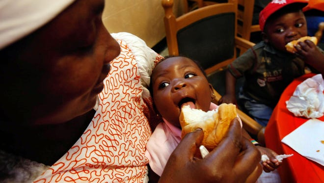 November, 2009 - Solange Idaba feeds her baby girl Lareine, during a Thanksgiving meal, which was for a wide variety of refugees at Catholic Charities on Friday. Her son Doumana is at right. She has eight children and came three months ago from a refugee camp in Cameroun, Africa. She has no idea what has happened to her husband. She is one of many refugees settled by Catholic Charities now living in Memphis.