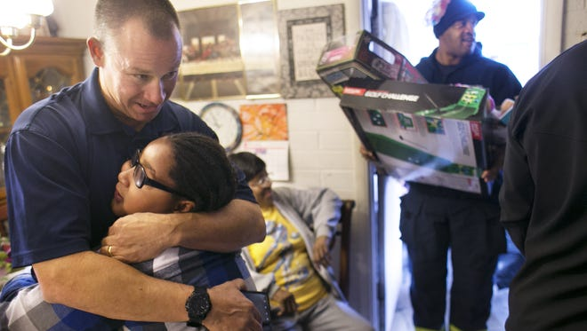 P.J. Dean, secretary of the United Phoenix Firefighters, hugs Areion Scroggins, 8, at a home Phoenix on Friday, December 16, 2016. Scroggins' grandmother's home was destroyed by fire on Thursday morning. Phoenix police and fire came together to deliver money, gift cards, Christmas presents and a Christmas tree to the family on Friday morning at the family home where they were staying across the street.