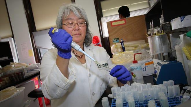 Neogen scientist Debra Foti tests egg samples for salmonella at the company's Allen Street lab in 2010. Neogen has recently acquired a Brazilian pesticide manufacturer.